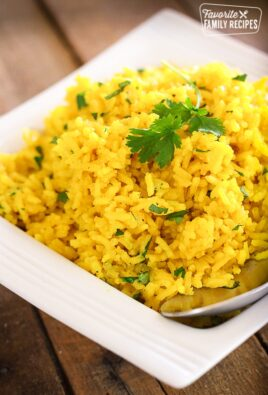 Yellow rice in a white serving dish topped with fresh cilantro