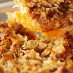Hot sweet potatoes with crunchy crumble topping being scooped from pan