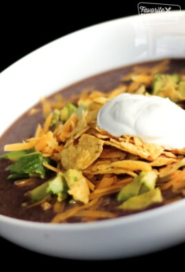 Black Bean Soup with corn chips, avocado and a dollop of sour cream in white bowl.