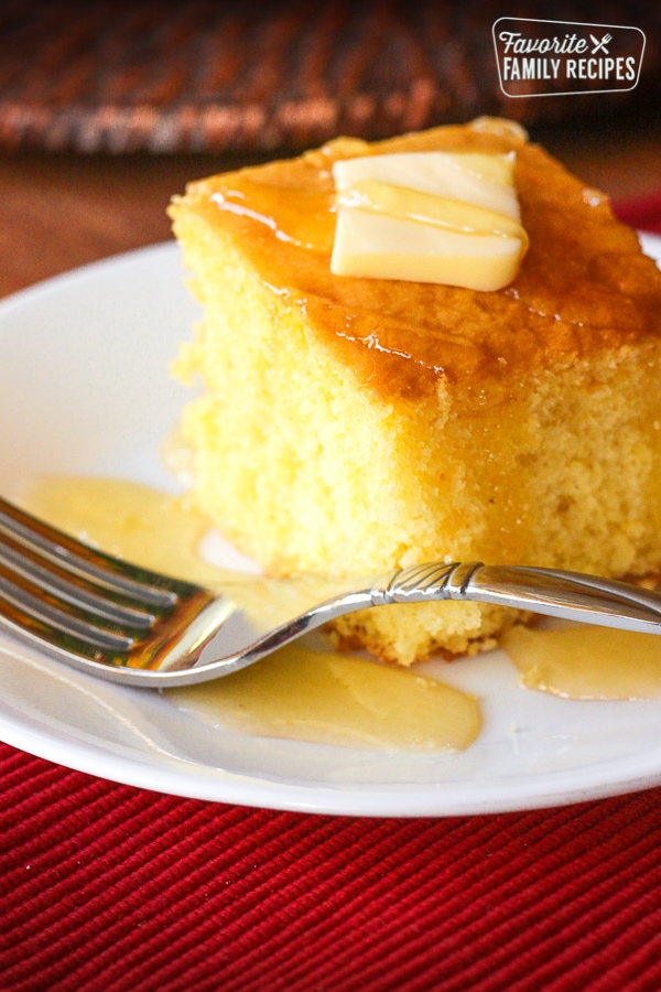 A slice of Cake Mix Cornbread on a white plate next to a fork.