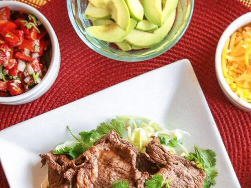 Grilled Carne Asada on a plate with avocado, cheese, and salsa on the side.