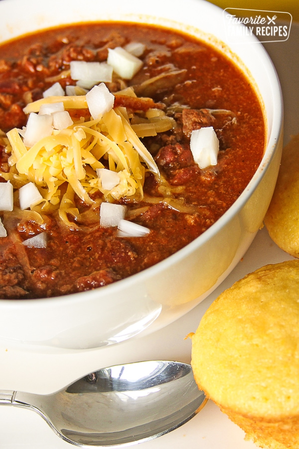 Cheater Chili topped with cheese and onions in a white bowl with cornbread on the side.
