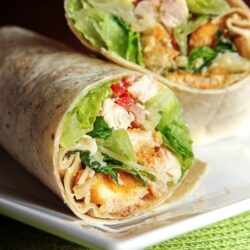 2 Chicken Caesar Wraps stacked on top of each other on a white plate.