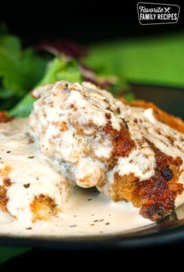 Chicken in Basil Cream Sauce with a salad on the side on a black plate.