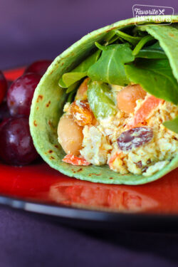 Chicken Salad Curry Wrap with grapes on the side on a red plate.