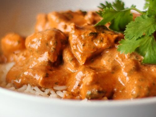 Chicken Tikka Masala over white rice in a white bowl with a garnish.