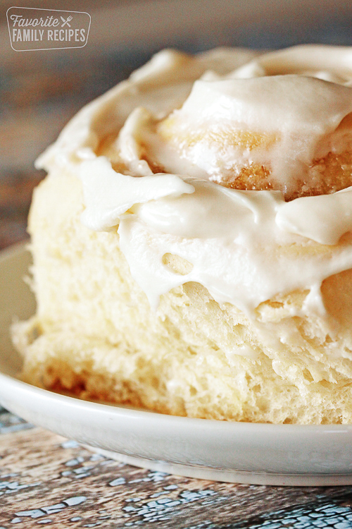 Close up of cinnamon roll on plate with frosting