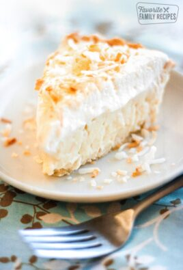 Slice of Coconut Cream Pie on a white Plate with a fork to the side.