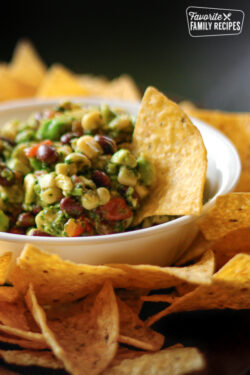 Cowboy Caviar in a white bowl surrounded by tortilla chips
