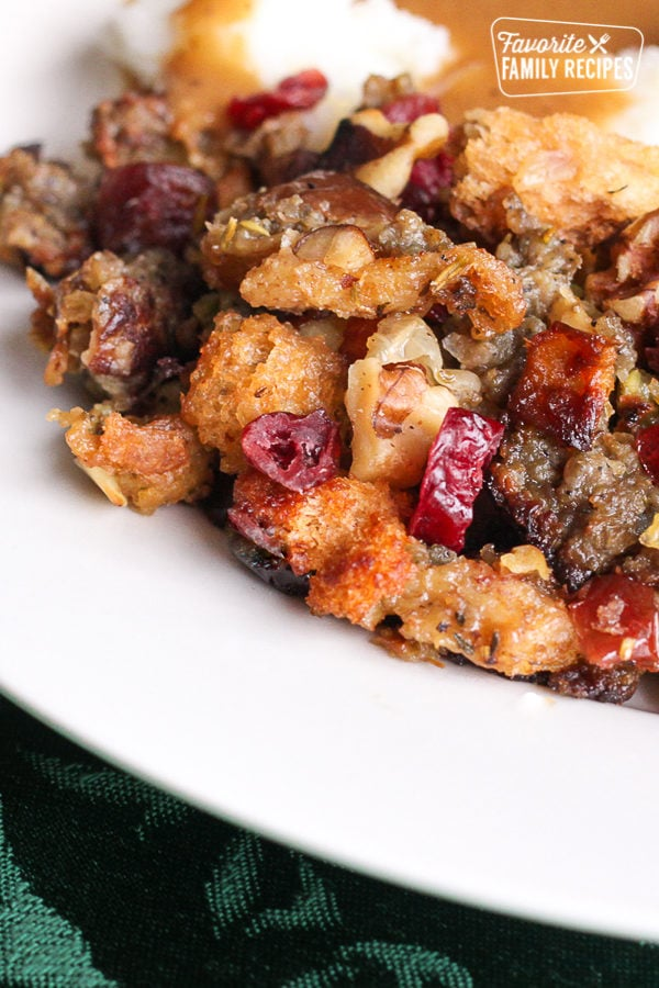 Cranberry sausage stuffing with sausage, dried cranberries, apples, and bread cubes served on a white plate