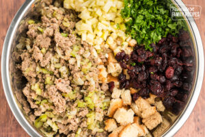 Sausage, cranberries, parsley, apples, bread cubes, and spices in a bowl