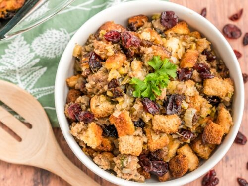 Cranberry Sausage Stuffing in a white bowl with a wooden spoon next to it