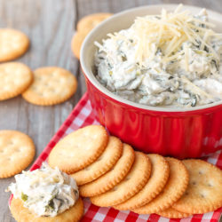 plate of crackers with easy spinach dip in red bowl