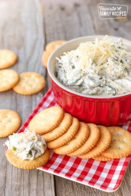 Easy Spinach Dip in a red bowl with Ritz crackers on a gingham napkin to the side