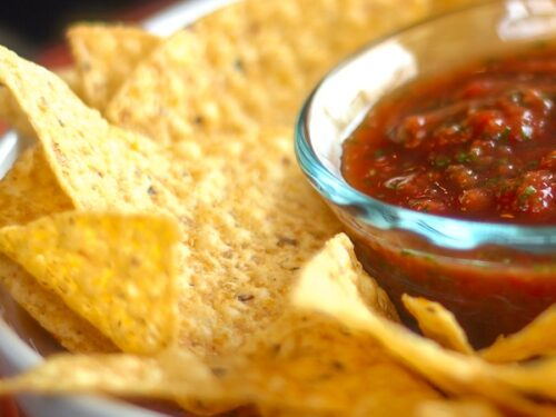 Homemade Salsa in a glass bowl surrounded by tortilla chips in a bigger white bowl.