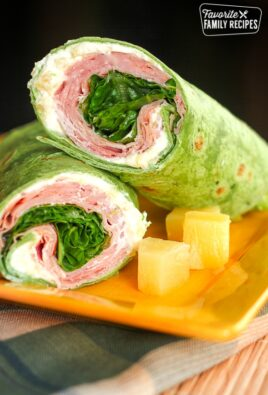 2 Ham Pineapple Wraps stacked on top of each other with a side of pineapple on a yellow plate.