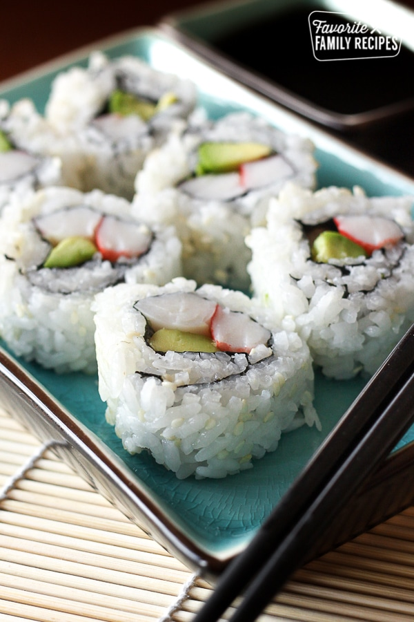 Homemade California Rolls on a blue plate with chopsticks and soy sauce on the side
