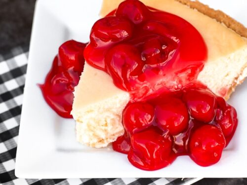A slice of homemade cheesecake on a white plate topped with cherries