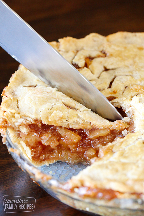 Knife slicing into a homemade apple pie