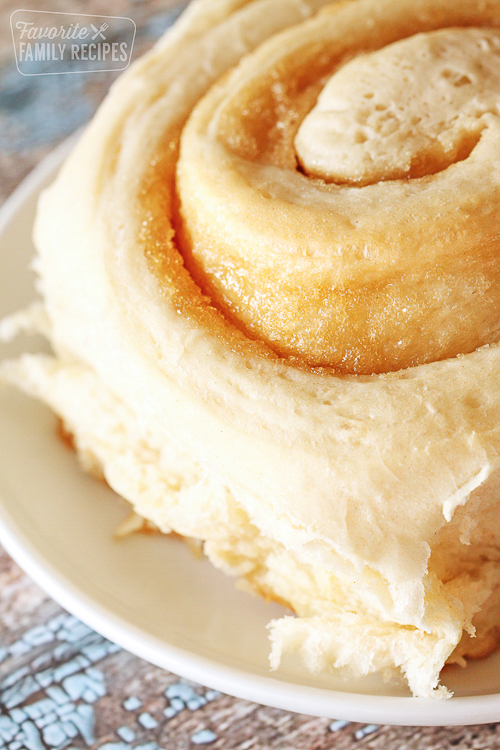 close up of homemade cinnamon roll on a white plate