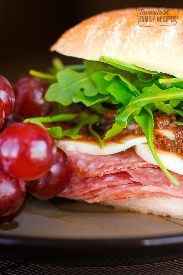Close up of an Italian Sandwich with Olive Tapenade and grapes on the side.