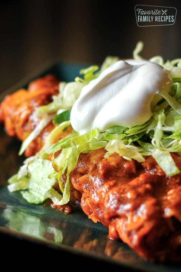 Enchiladas from Scratch topped with lettuce and sour cream on a plate.