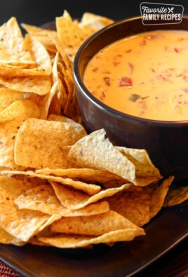 Easy Nacho Cheese Dip in a bowl with Tortilla Chips on the side.