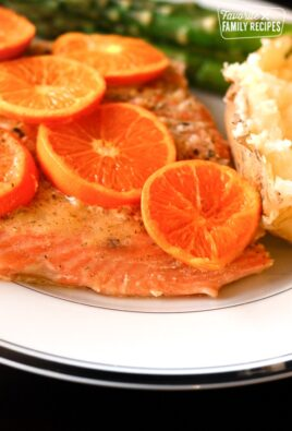 Orange Grilled Salmon topped with orange slices and potatoes and asparagus on the side on a white plate.