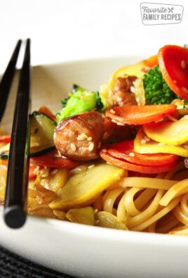 Oriental Pasta in a white bowl with chopsticks on the side.