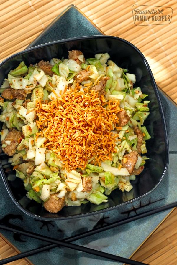Ramen Noodle Salad in a black bowl with chopsticks on the side