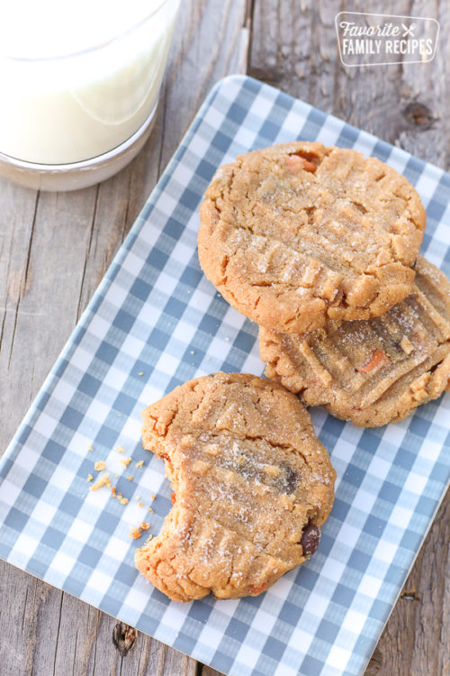 peanut butter cookies with bit out of one and glass of milk