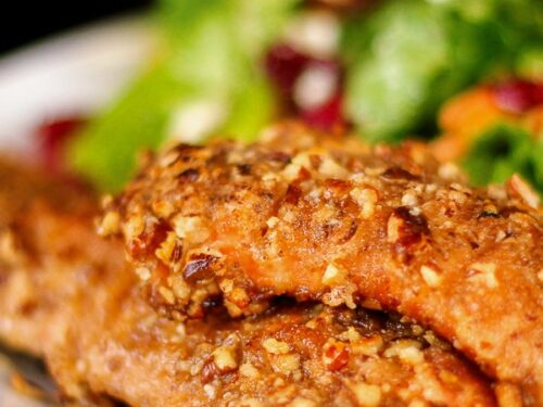2 pieces of Pecan Crusted Salmon with a salad on the side on a white plate.
