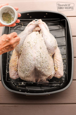 Herbs being sprinkled on a raw turkey in a roasting pan