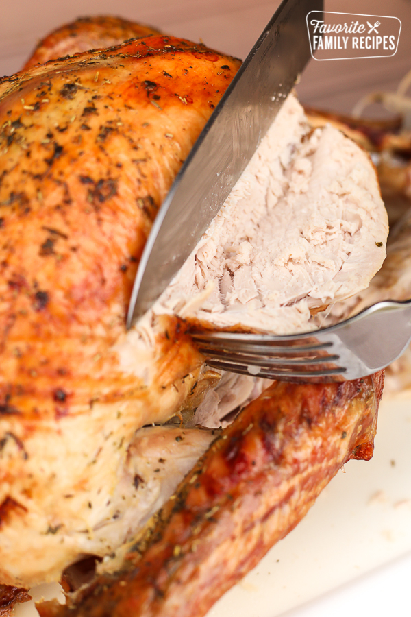 A roasted turkey being carved with a fork and a knife