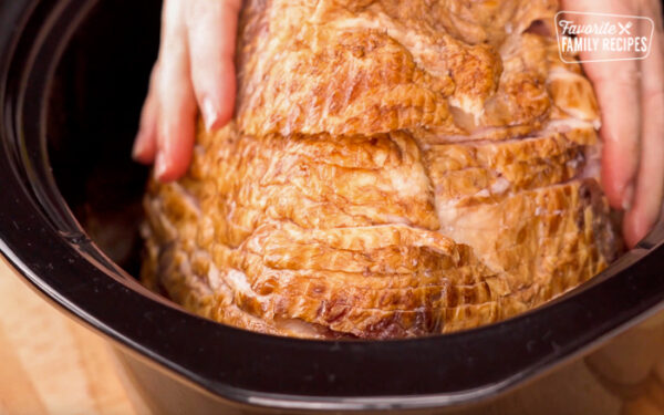 Ham being placed in a slow cooker flat side down