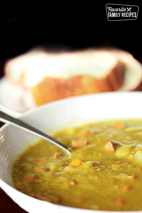 bowl of split pea soup with bread in background