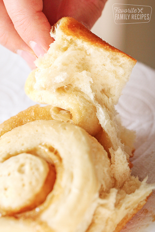 hand pulling up piece of homemade cinnamon roll