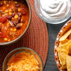 Southwest Taco Soup in a bowl with sour cream, cheese, and chips on the side.