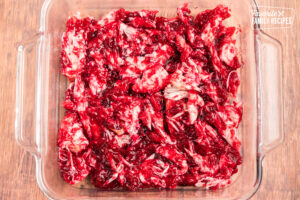 Turkey and cranberry sauce mixed together and spread on the bottom of a glass baking dish