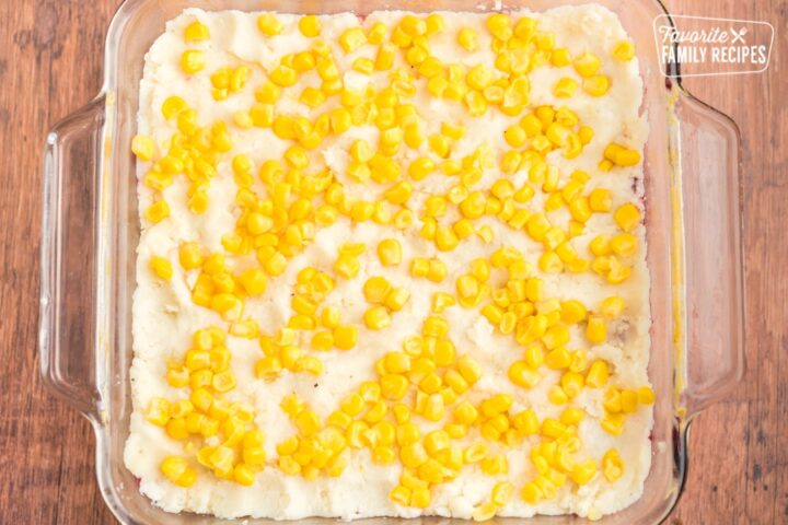 Mashed potatoes and corn spread out in a casserole dish