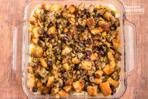 Stuffing on top of a thanksgiving leftover casserole in a glass baking dish