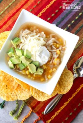 Chicken tortilla soup in bowl with sour cream and avocado with tortilla chips on the side.