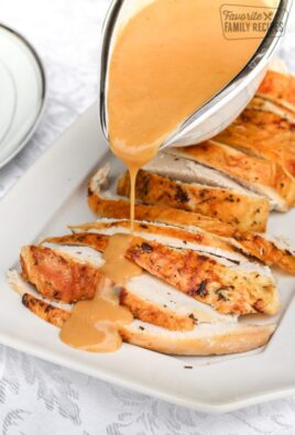 Turkey gravy being poured over sliced turkey