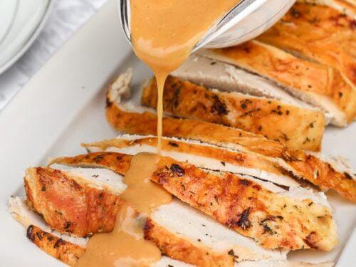 Turkey gravy being poured over sliced turkey