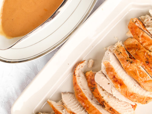 A gravy boat filled with turkey gravy next to a platter of sliced roasted turkey