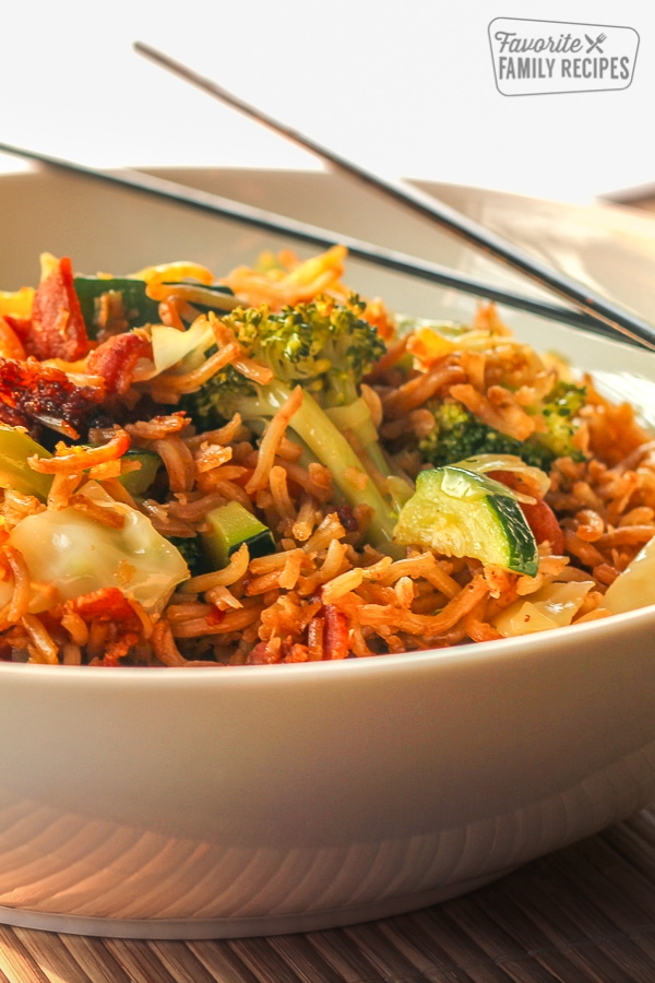 Yakisoba Japanese stir-fry noodles with bacon and vegetables in a bowl with chopsticks on the side