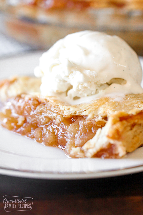 Slice of apple pie with ice cream over the top