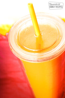 Orange Julius in a clear cup with a straw.