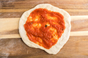 Marinara sauce spread on pizza dough