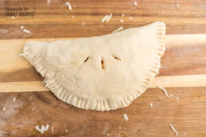 An uncooked calzone on a cutting board